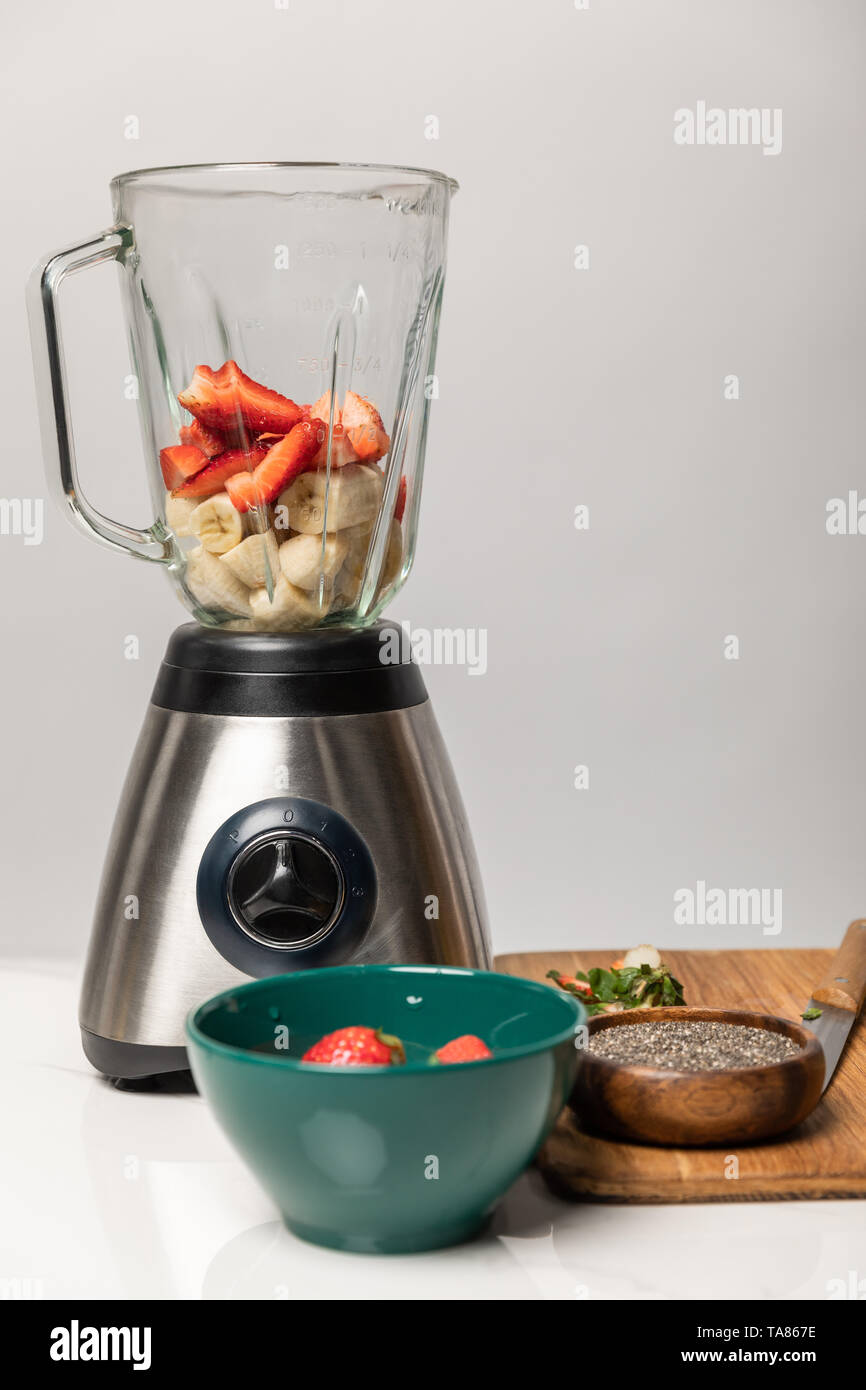 sweet strawberries and ripe bananas in blender near bowls and cutting board on grey - Stock Image