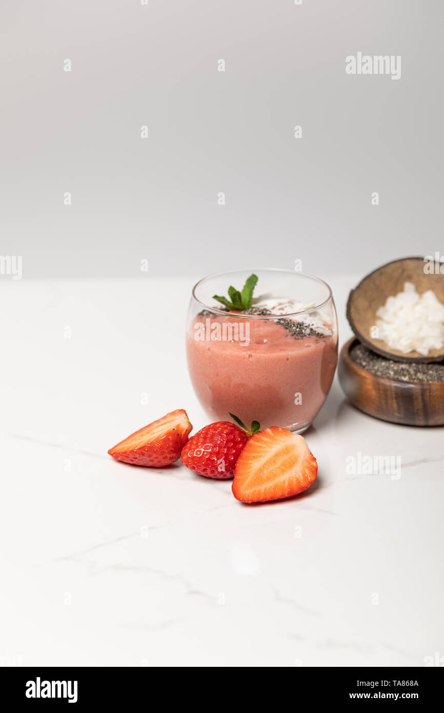 tasty smoothie with coconut flakes in glass near tasty strawberries on grey - Stock Image