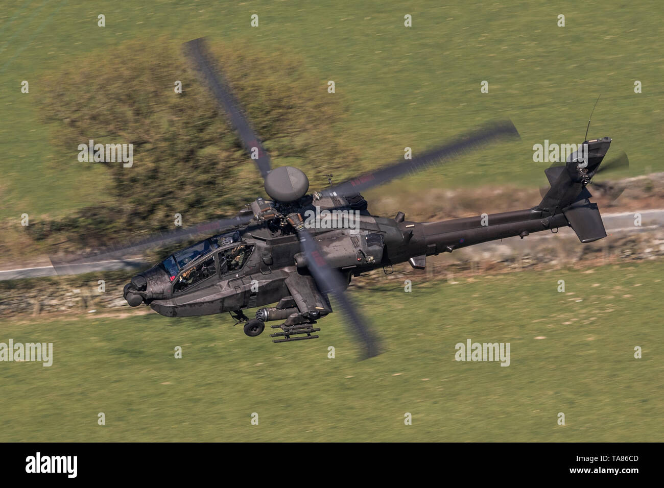 Army Air Corps WAH-64 Apache flying low level in the Mach Loop in Wales, UK Stock Photo
