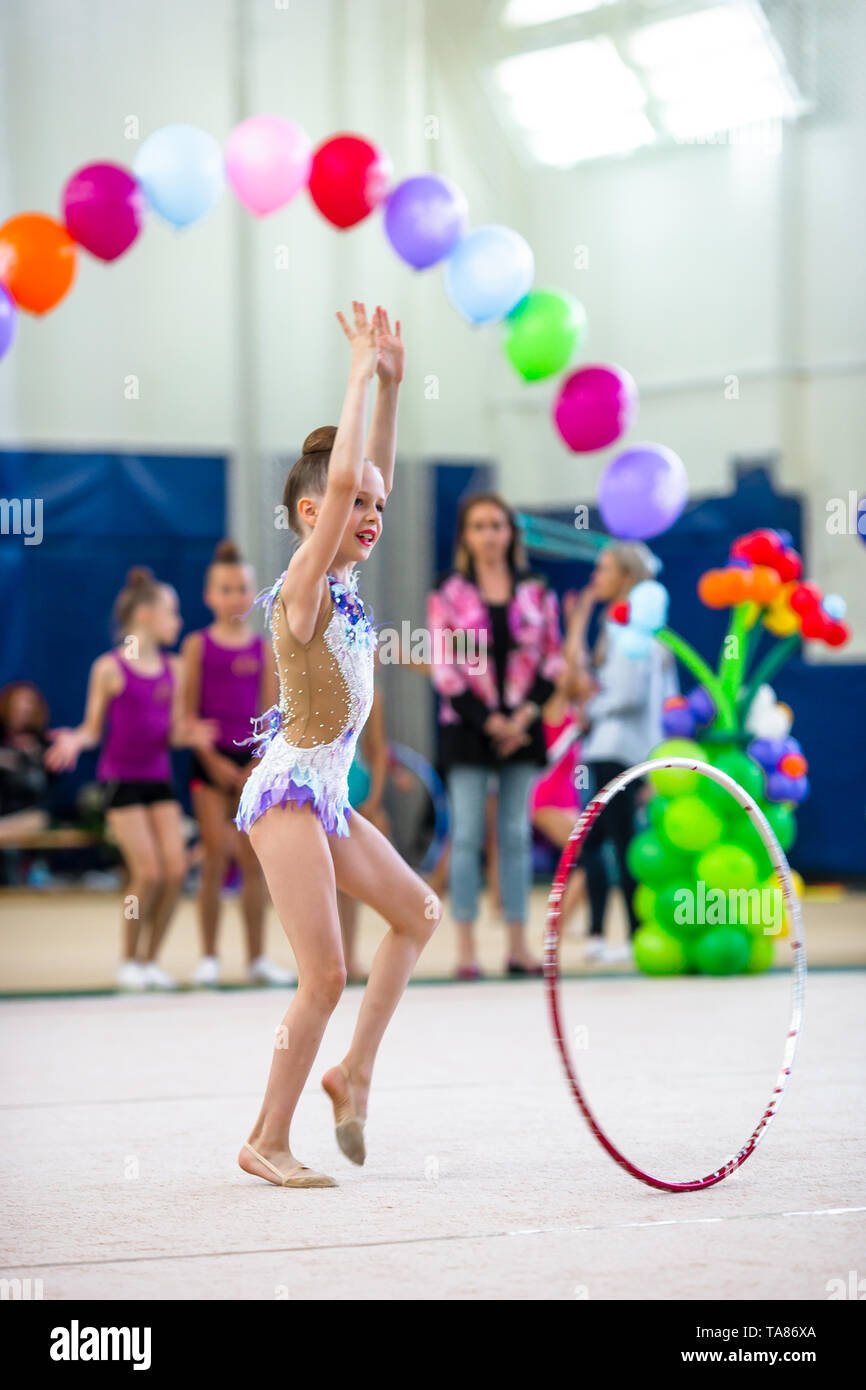 Beautiful little active gymnast girl with her performance on the carpet - Stock Image