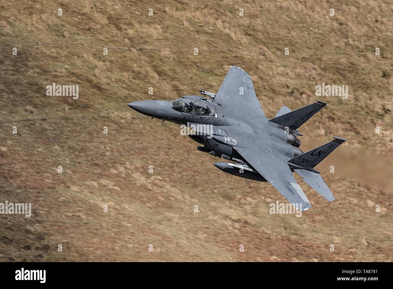 USAF F-15E Strike Eagle flying low level through the Mach Loop in Wales, UK Stock Photo
