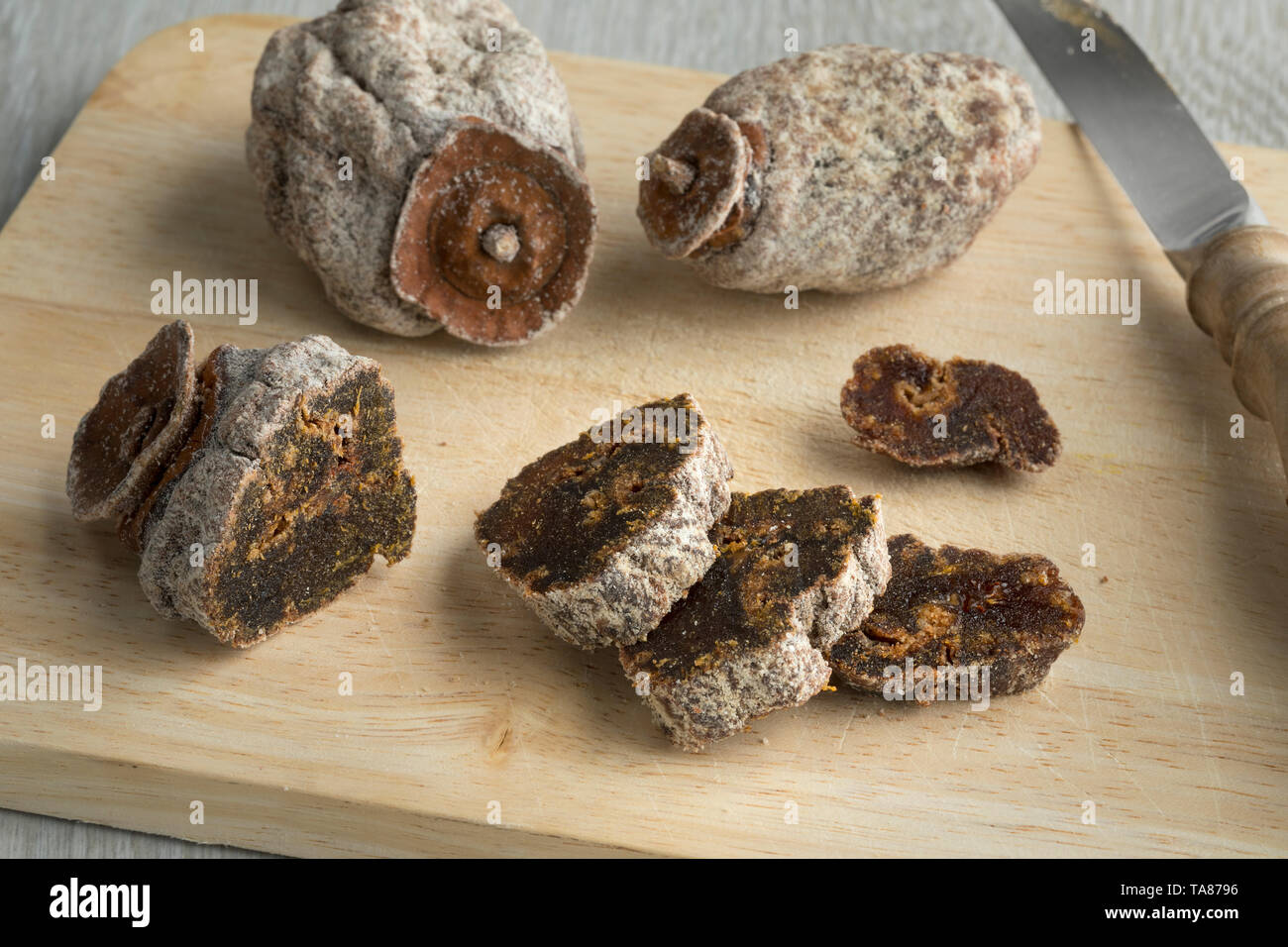 Dried kaki fruit and slices on a cutting board - Stock Image