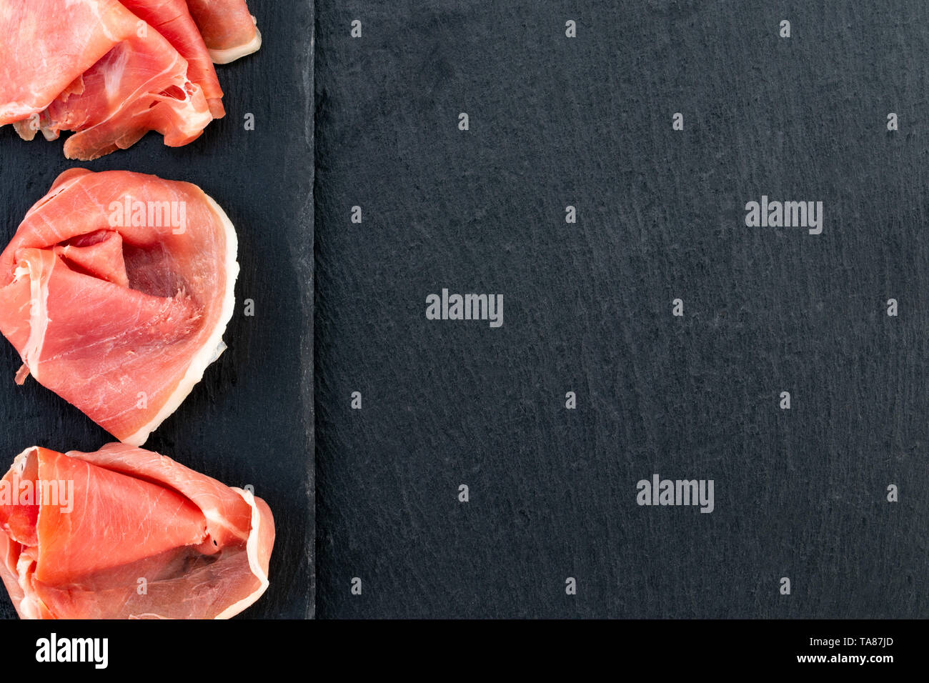 Italian prosciutto crudo or spanish jamon and sausages. Raw ham on stone cutting board, copy space, top view. - Stock Image