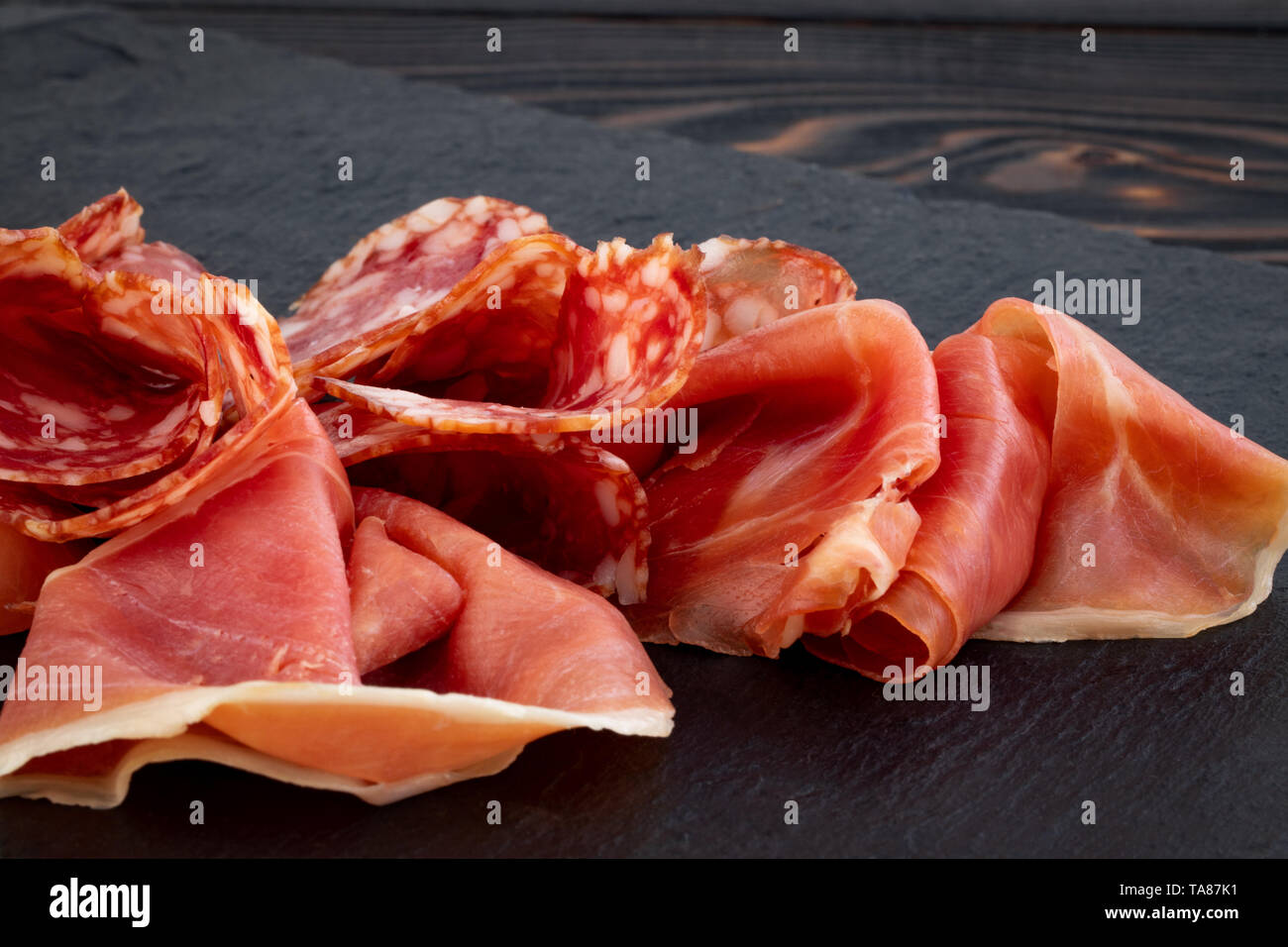 Italian prosciutto crudo or spanish jamon and sausages. Raw ham on stone cutting board. - Stock Image