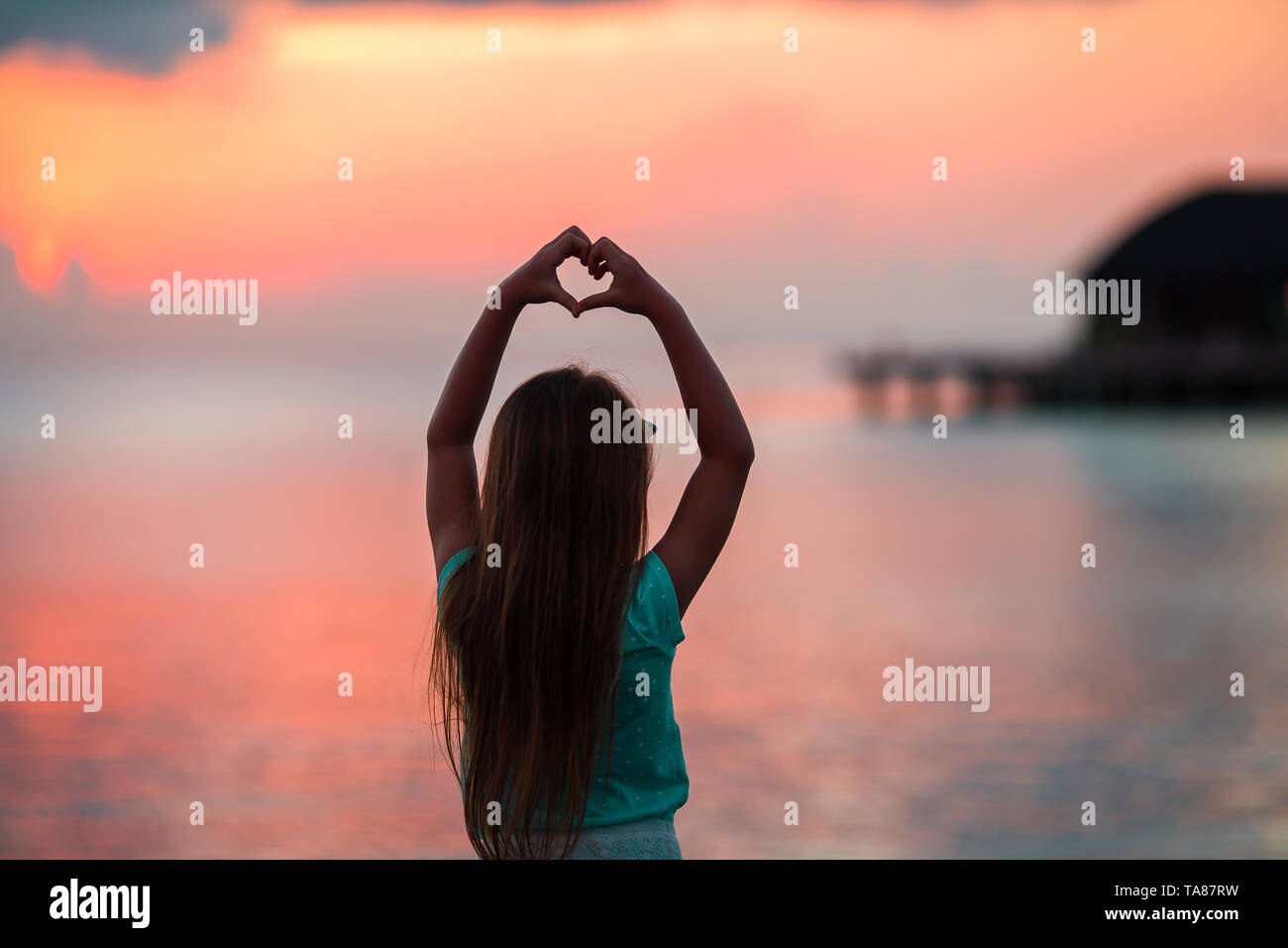 Silhouette of heart made by kids hand at sunset Stock Photo