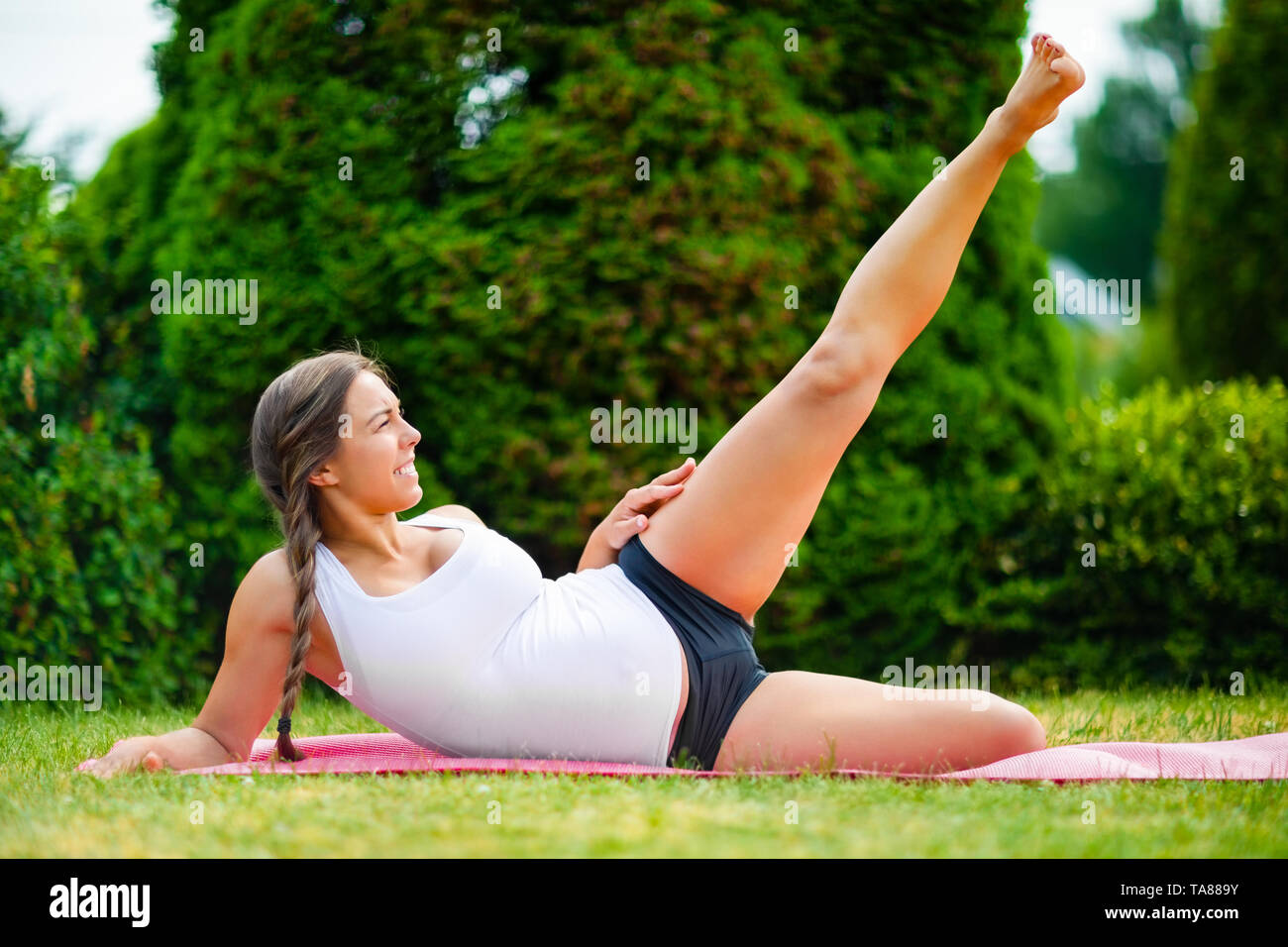 Expectant Woman Doing Side Reclining Leg Lift In Park - Stock Image