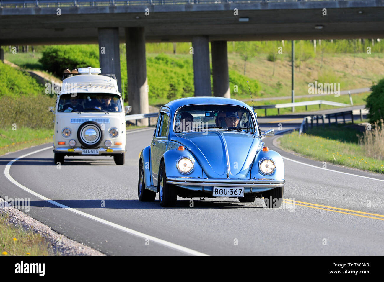 Salo, Finland. May 18, 2019. Classic 1970s Volkswagen Beetle, or Type 1 and white VW camper van, or Type 2 on road on Salon Maisema Cruising 2019. - Stock Image