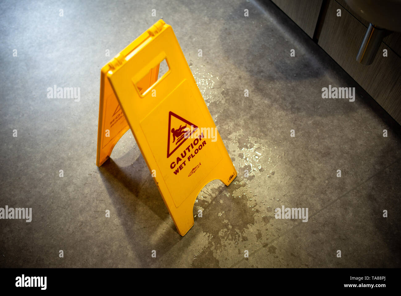 Caution wet floor safety stand up yellow warning sign in a toilet. - Stock Image