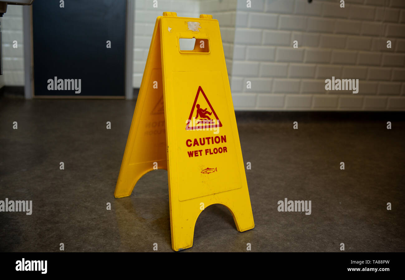 Caution wet floor safety stand up yellow warning sign in a toilet. Stock Photo