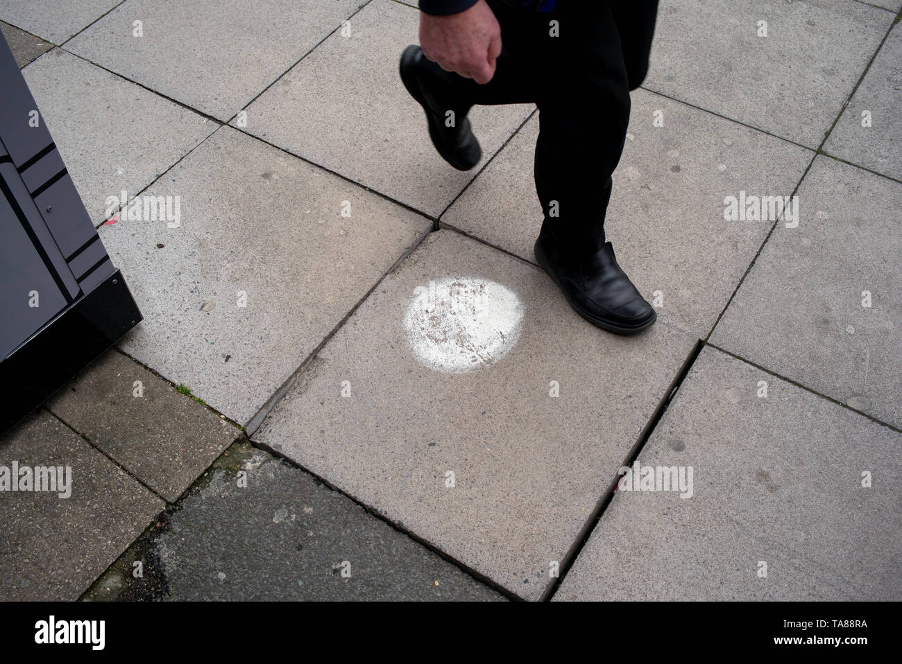 A marked paving stone with a paint spot stepped upon in Southampton city centre which needs attention as it moves and is dangerous as a trip hazard. - Stock Image