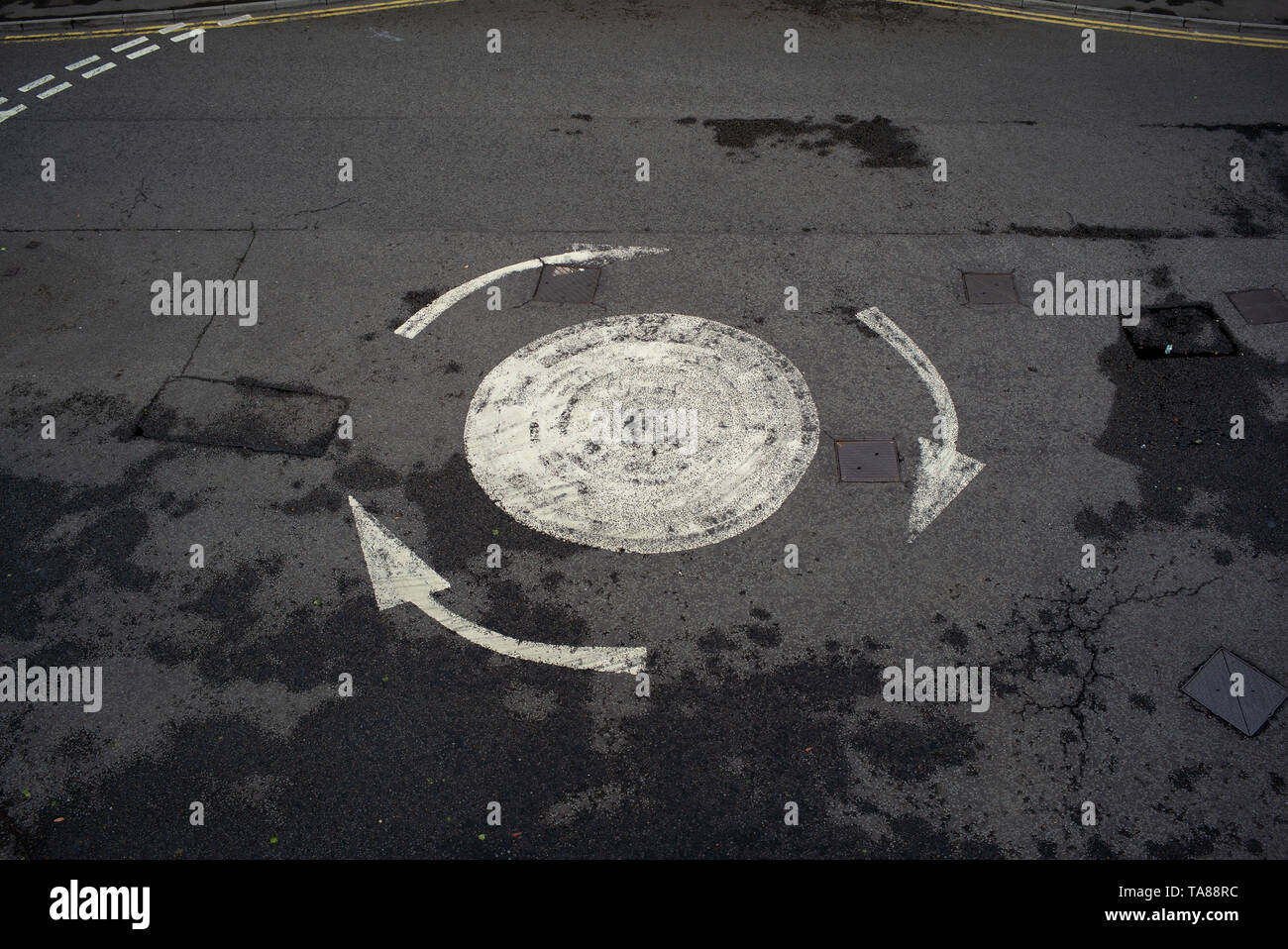 An aerial view of a painted road arrowed roundabout with no cars on could be used for analogy or concept image of being confused or lost etc. Stock Photo