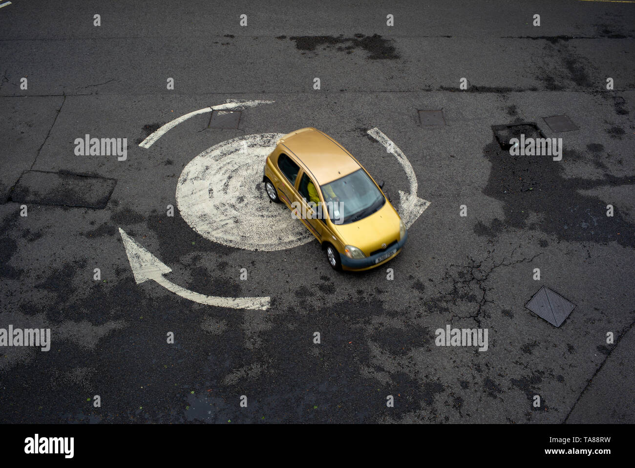 Aerial view of a painted arrowed roundabout with a single car going around. Could be used as an analogy or concept as being lost or going in circles. Stock Photo