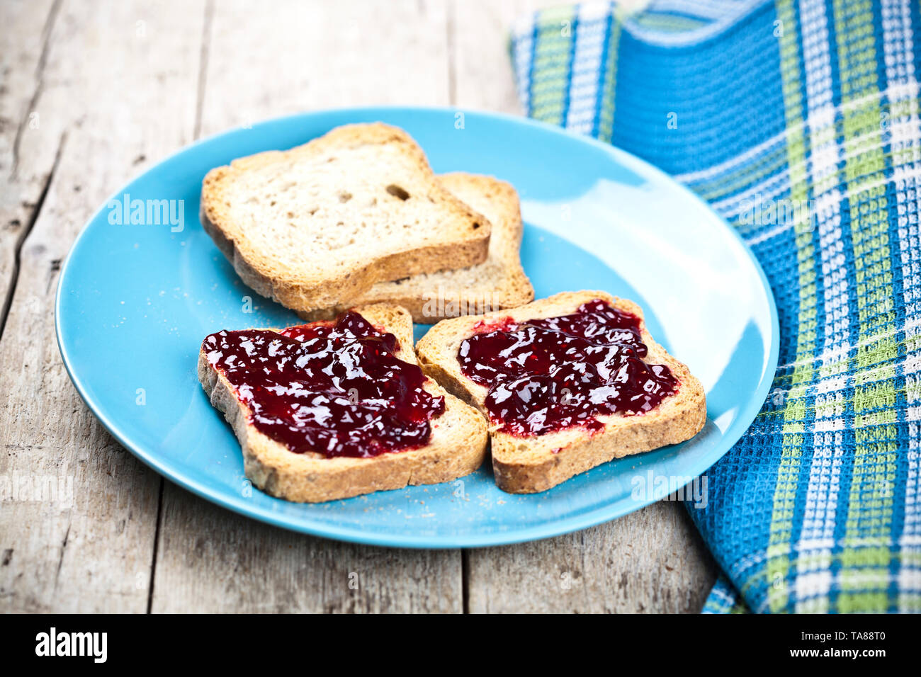 Fresh toasted cereal bread slices with homemade wild berries jam and linen napkin on blue ceramic plate closeup on rustic wooden background. Sweet foo - Stock Image