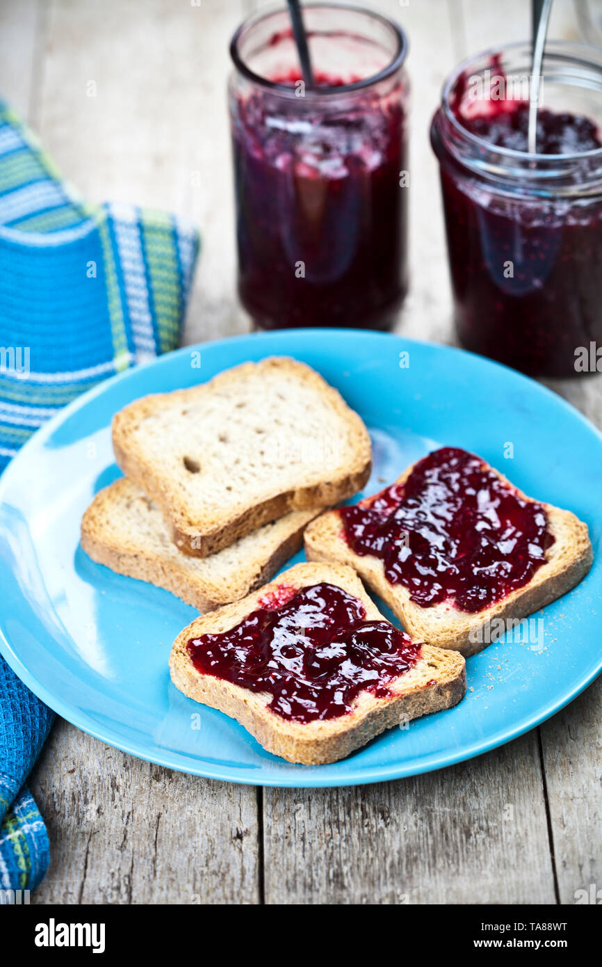 Fresh cereal bread slices on blue ceramic plate, homemade cherry and wild berries jam in jars and spoons closeup on linen napkin on rustic wooden tabl - Stock Image