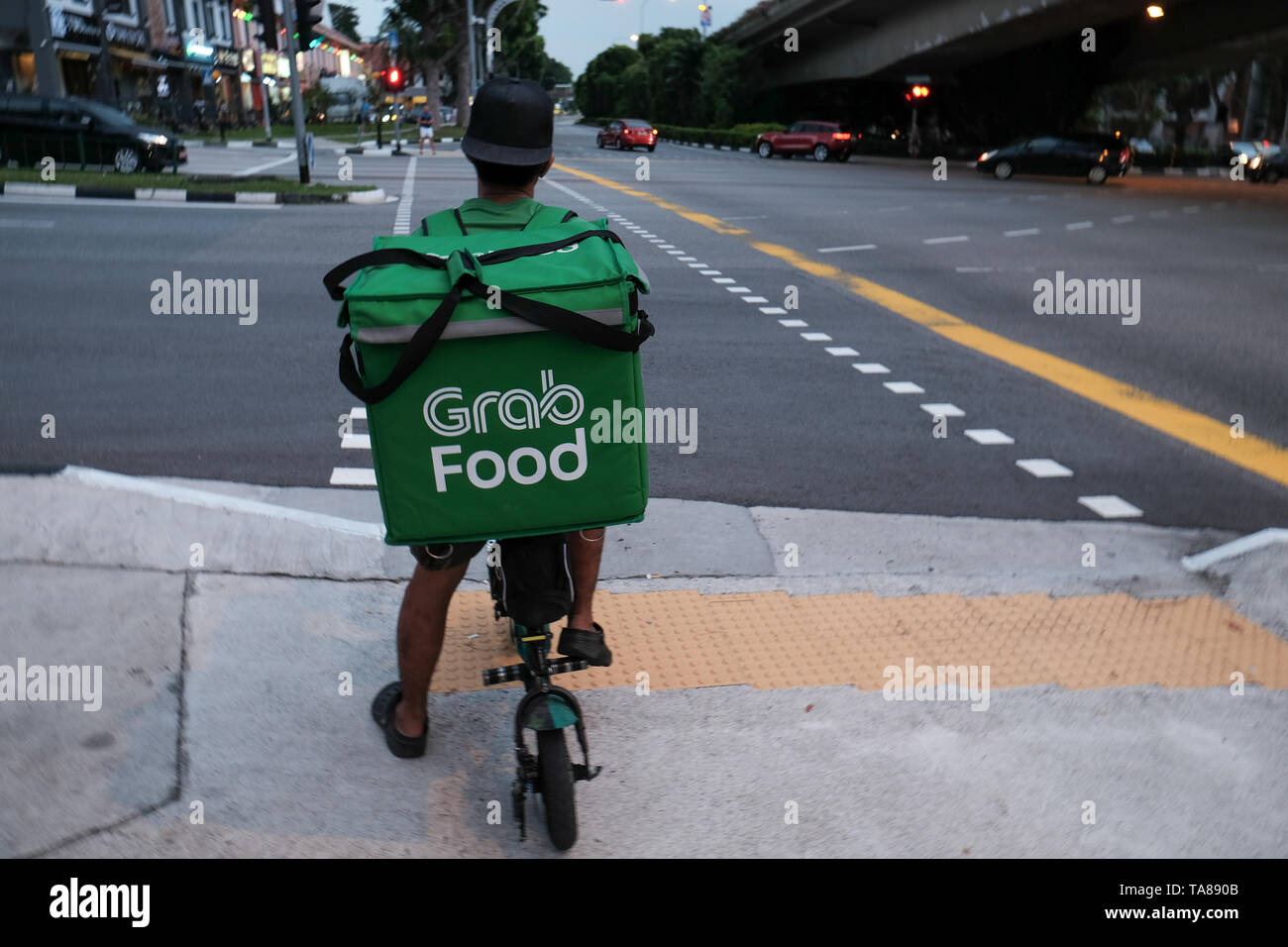 A Grab Food cycle rider on the streets of Singapore delivering food waiting at a crossing of a busy road as a rain storm moves in for a dramatic image. Stock Photo
