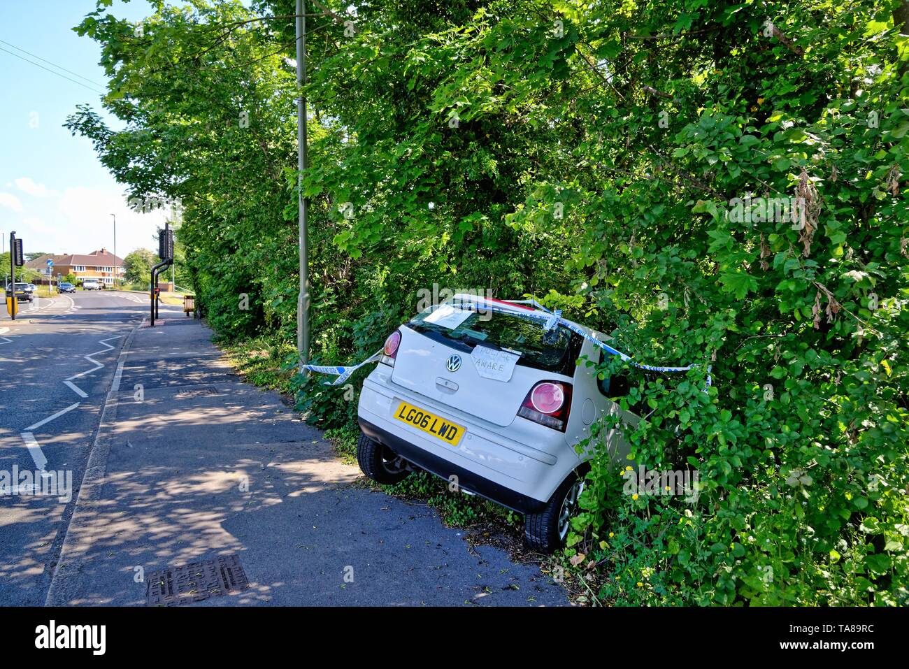 A white saloon car face down in a ditch after crashing off a main road, Shepperton Surrey England UK Stock Photo
