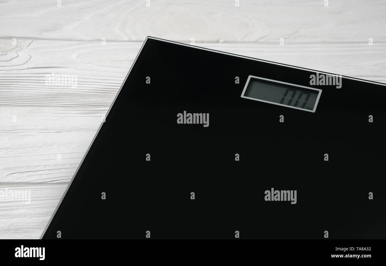 Digital bathroom weight scale on white wooden background - Stock Image
