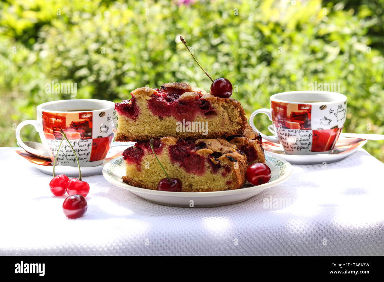 Pieces of a pie with a cherry and two cups of coffee on a table outdoors - Stock Image