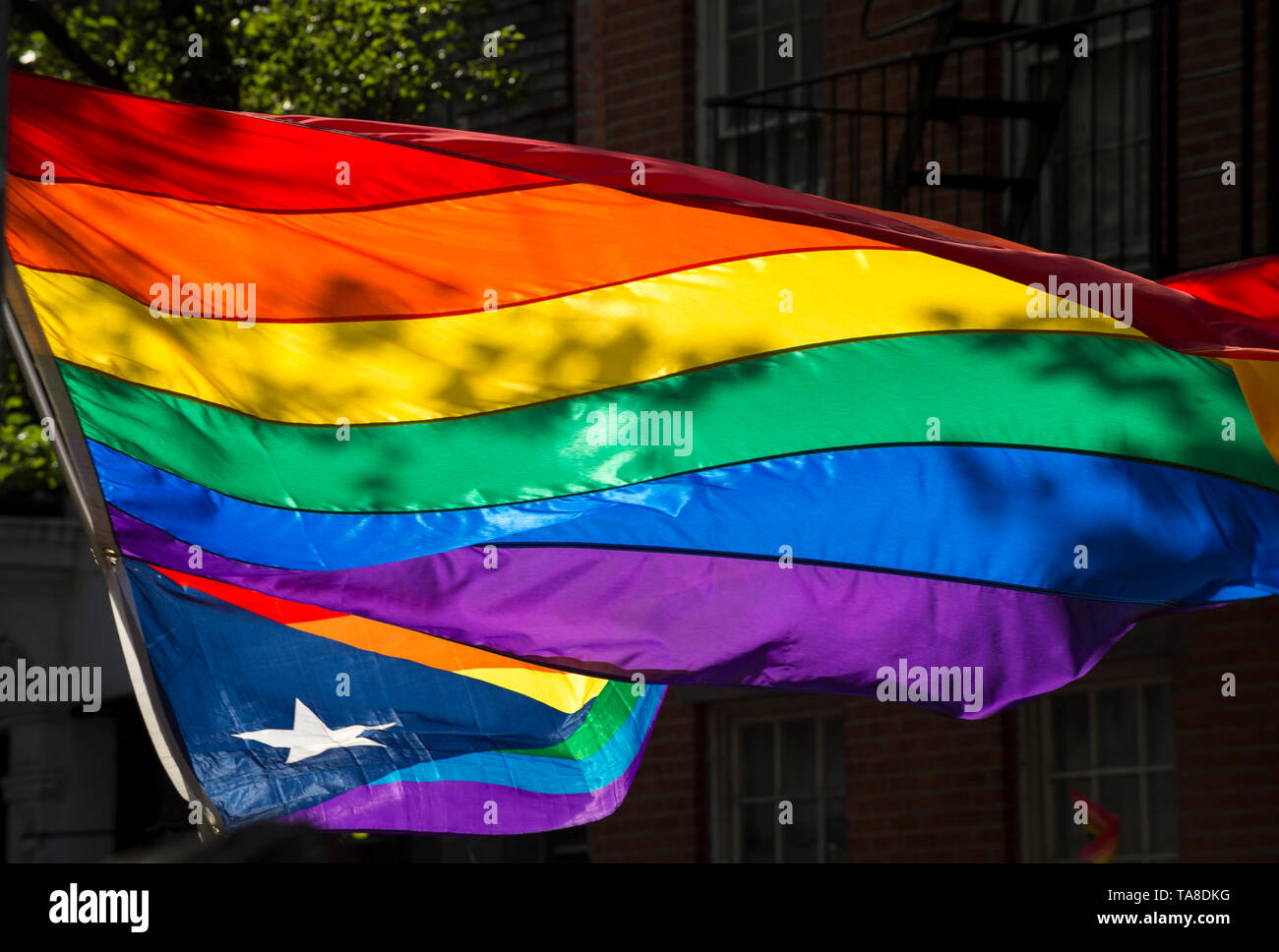 Rainbow flag waving in the shadows with a Puerto Rican gay pride flag at a summer pride parade in New York City Stock Photo