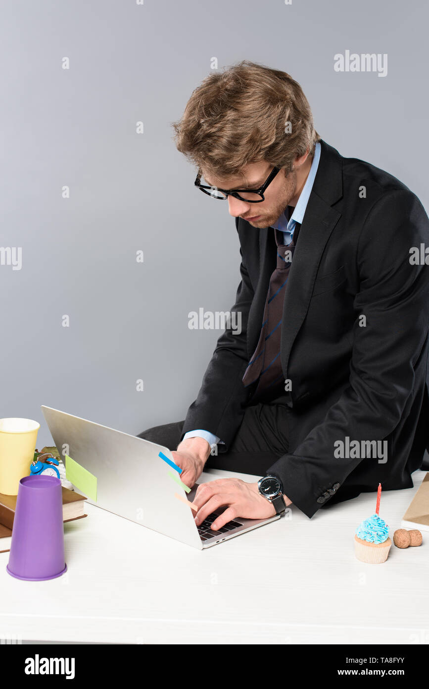 businessman in glasses using laptop while sitting at messy workplace isolated on grey - Stock Image