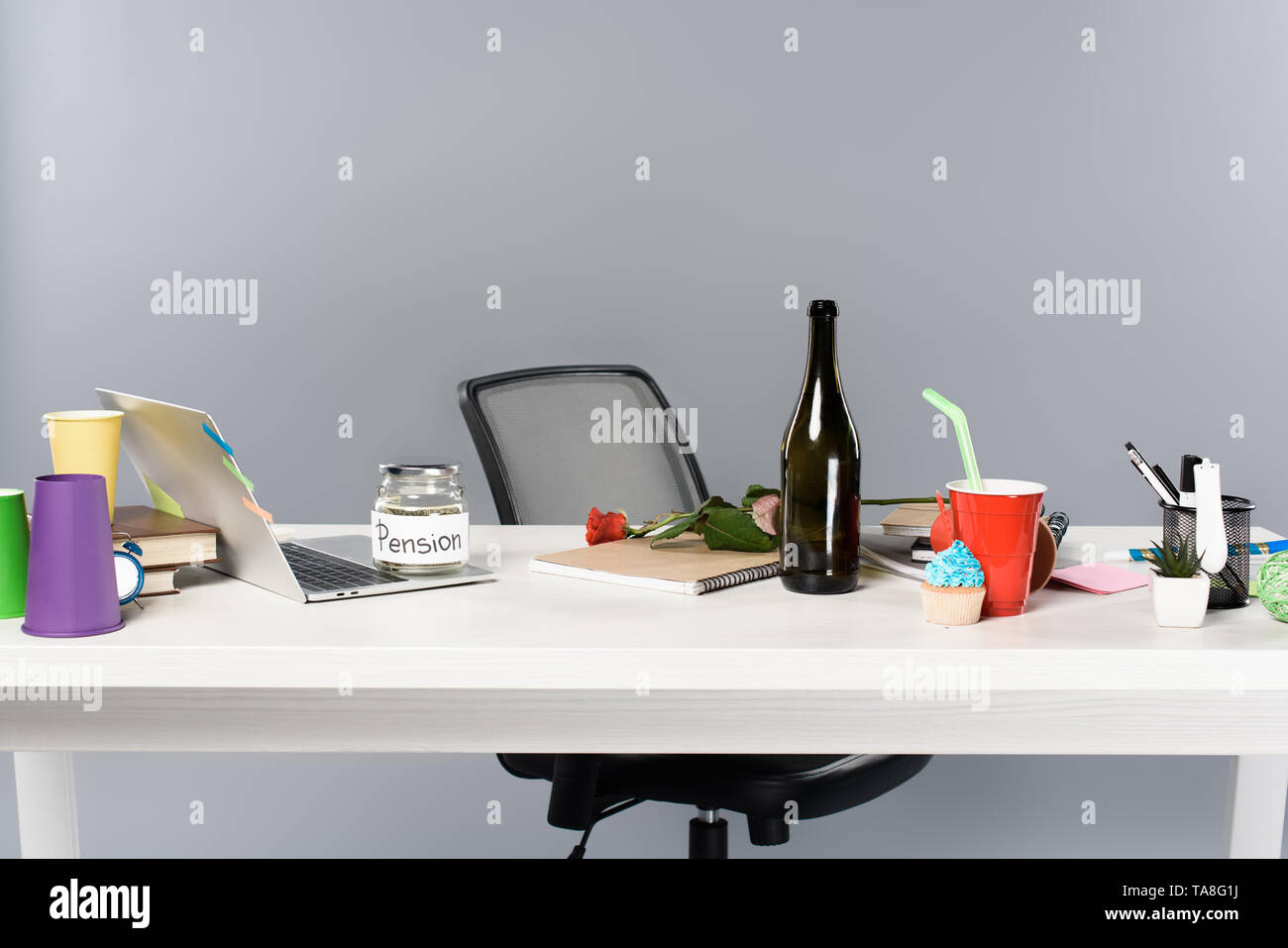 messy workplace with champagne bottle, paper cups, pension moneybox and laptop on white table - Stock Image