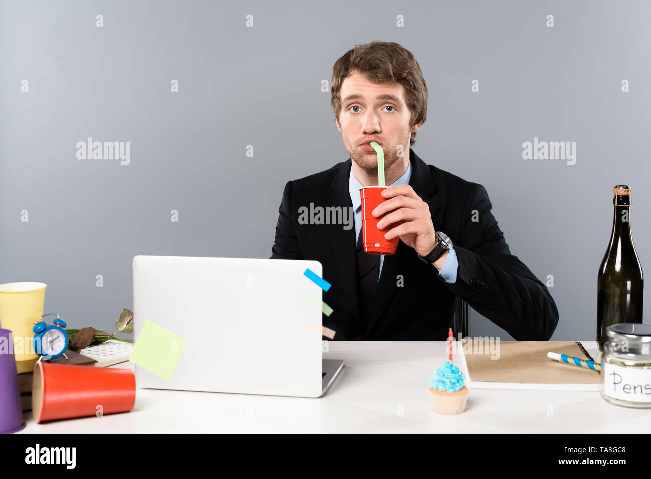 businessman sitting at workplace with cupcake and drinking from paper cup isolated on grey - Stock Image