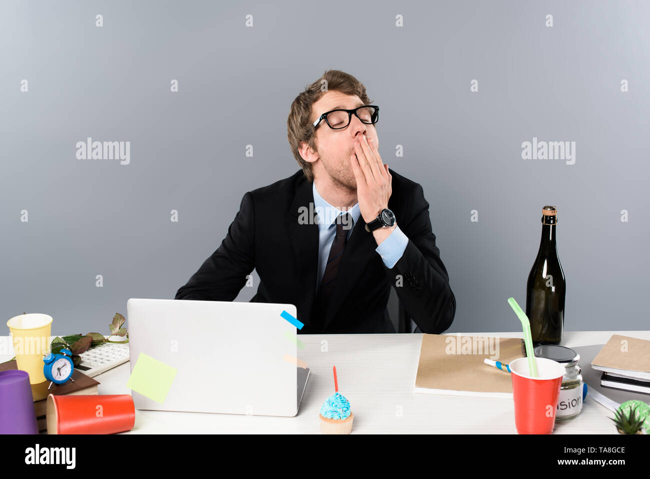 businessman yawing at workplace near cupcake and paper cups isolated on grey - Stock Image