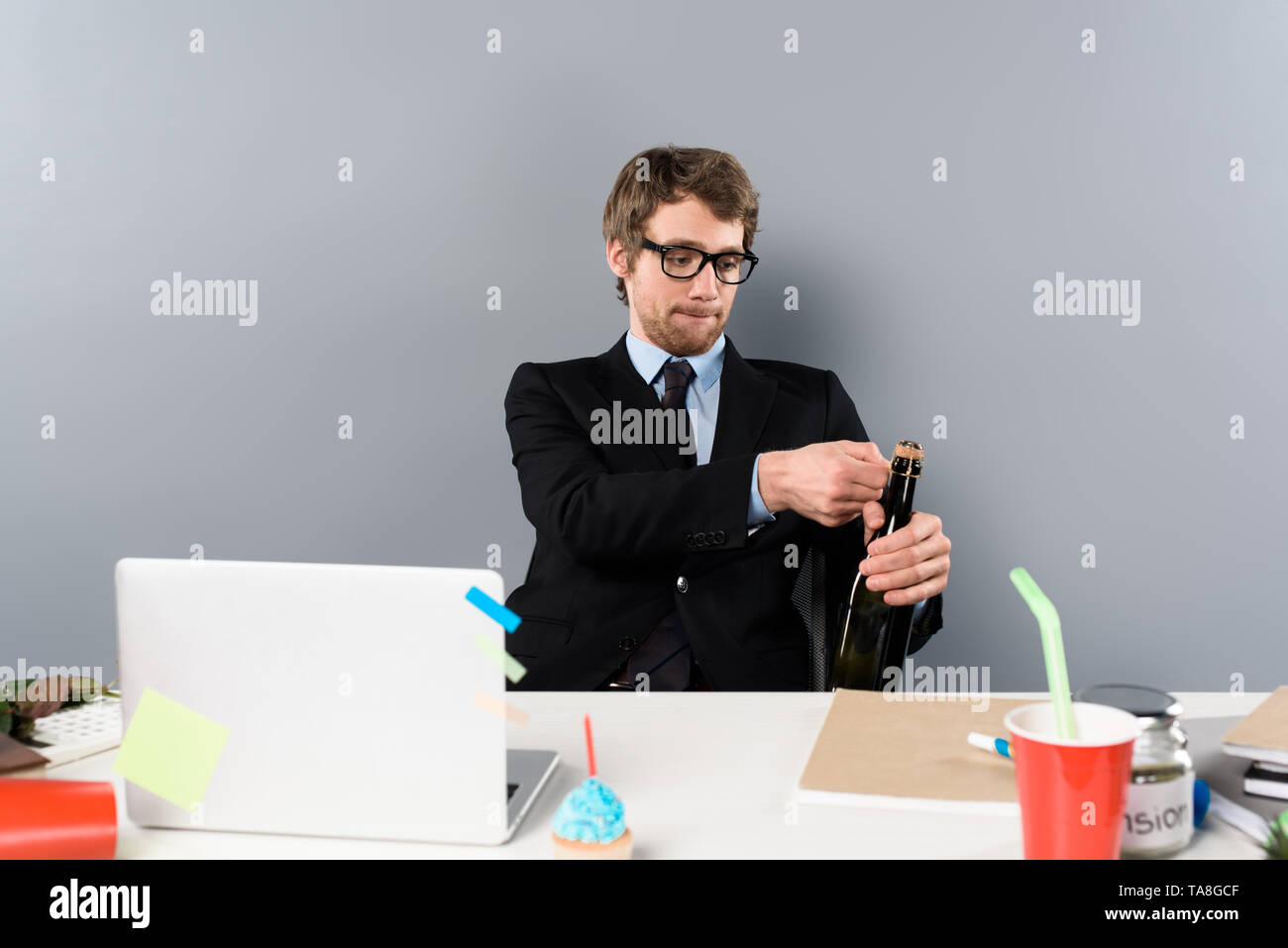 businessman sitting at workplace and opening bottle with champagne isolated on grey - Stock Image