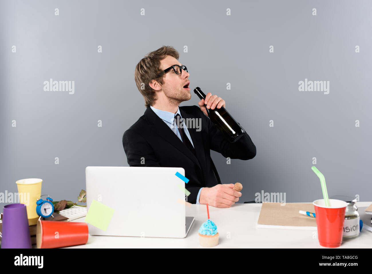 businessman sitting at workplace with cupcake and drinking champagne from bottle isolated on grey - Stock Image