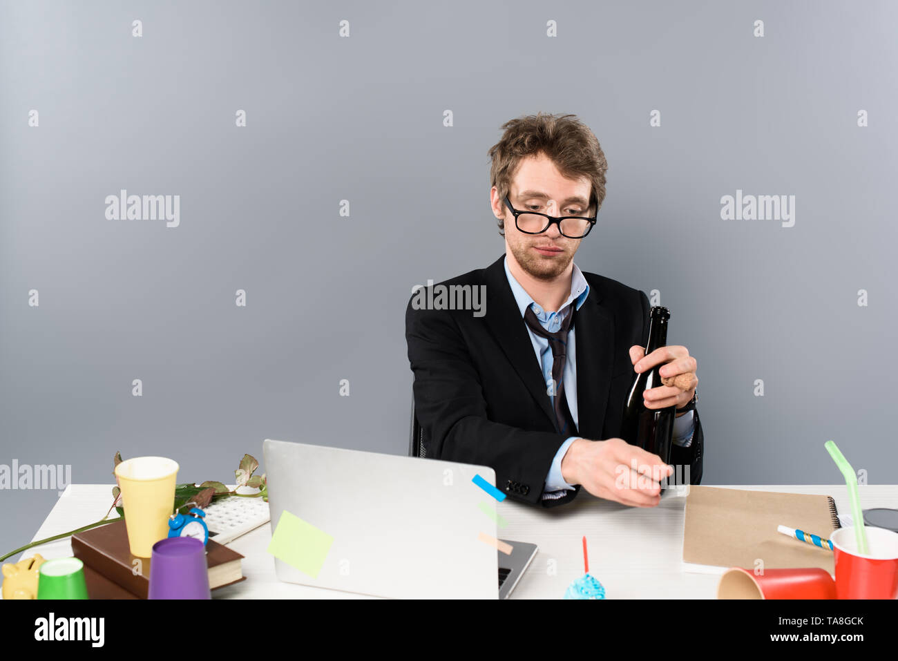 drunk businessman sitting at workplace with bottle of champagne isolated on grey - Stock Image