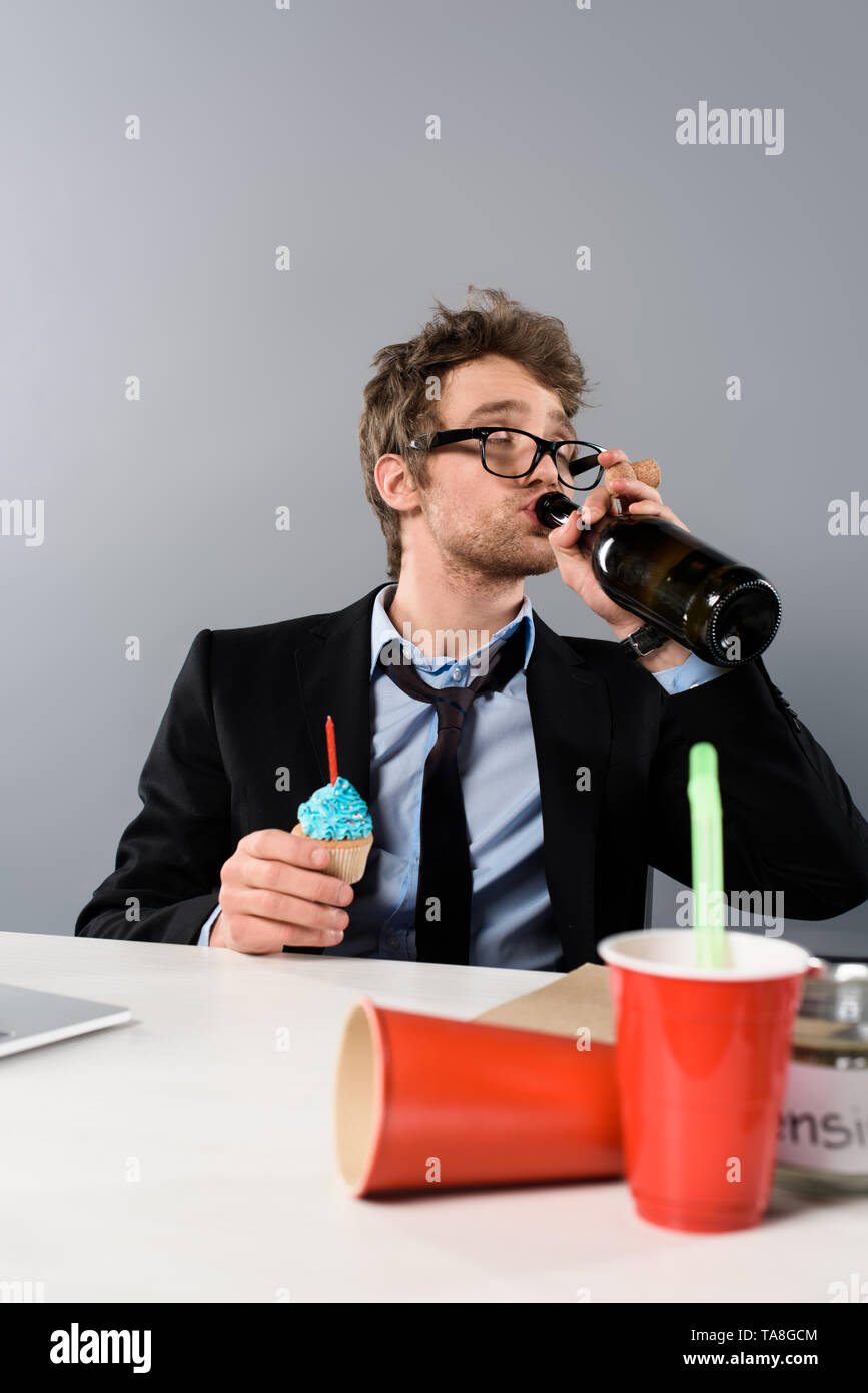 drunk businessman sitting at workplace and drinking champagne from bottle isolated on grey - Stock Image