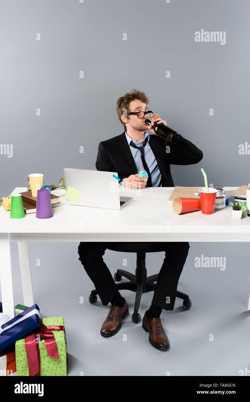 drunk businessman sitting at workplace and drinking champagne from bottle near gift boxes - Stock Image