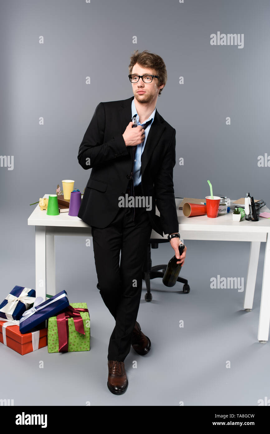 drunk businessman standing near workplace and gift boxes with champagne - Stock Image