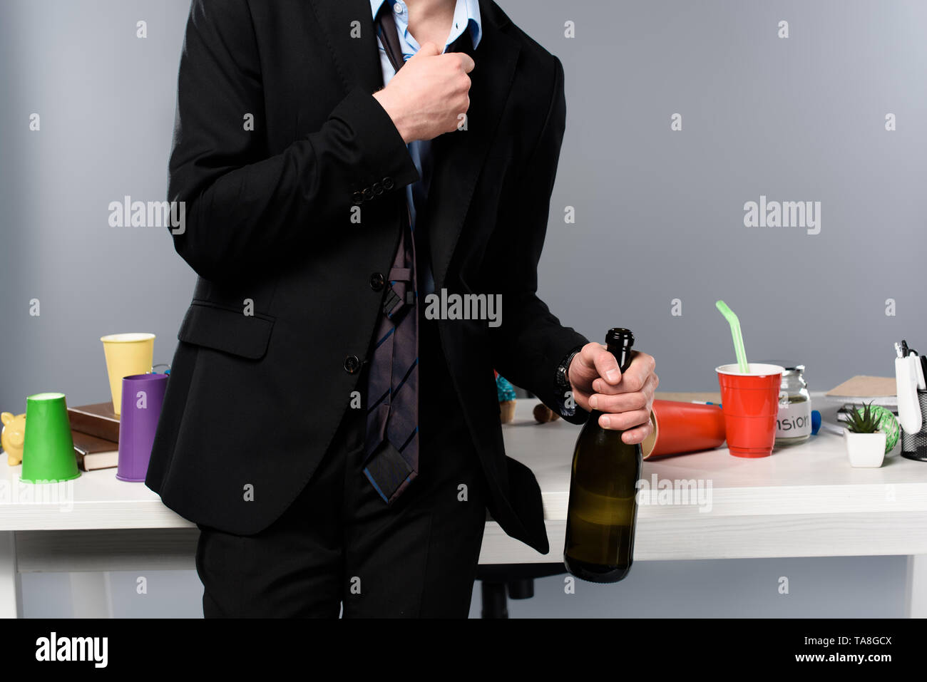 cropped view of drunk businessman standing near workplace with bottle of champagne - Stock Image