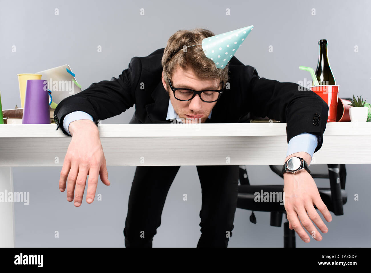 businessman in glasses and party cap  sleeping at messy workplace isolated on grey - Stock Image