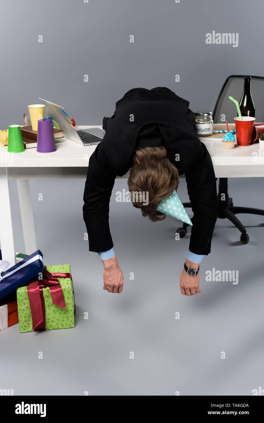 businessman in party cap sleeping on table at messy workplace - Stock Image