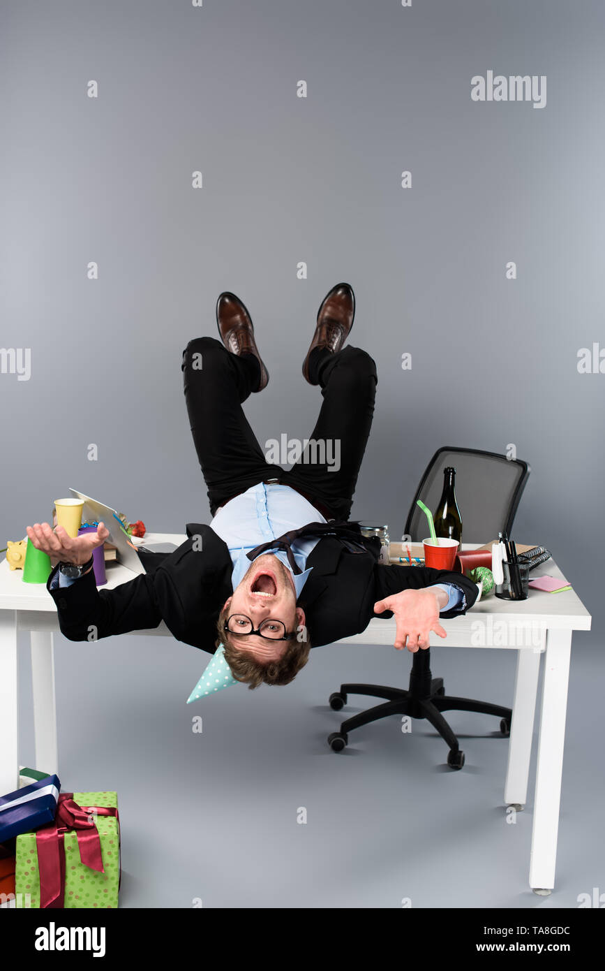 happy businessman in party cap lying on table at messy workplace - Stock Image