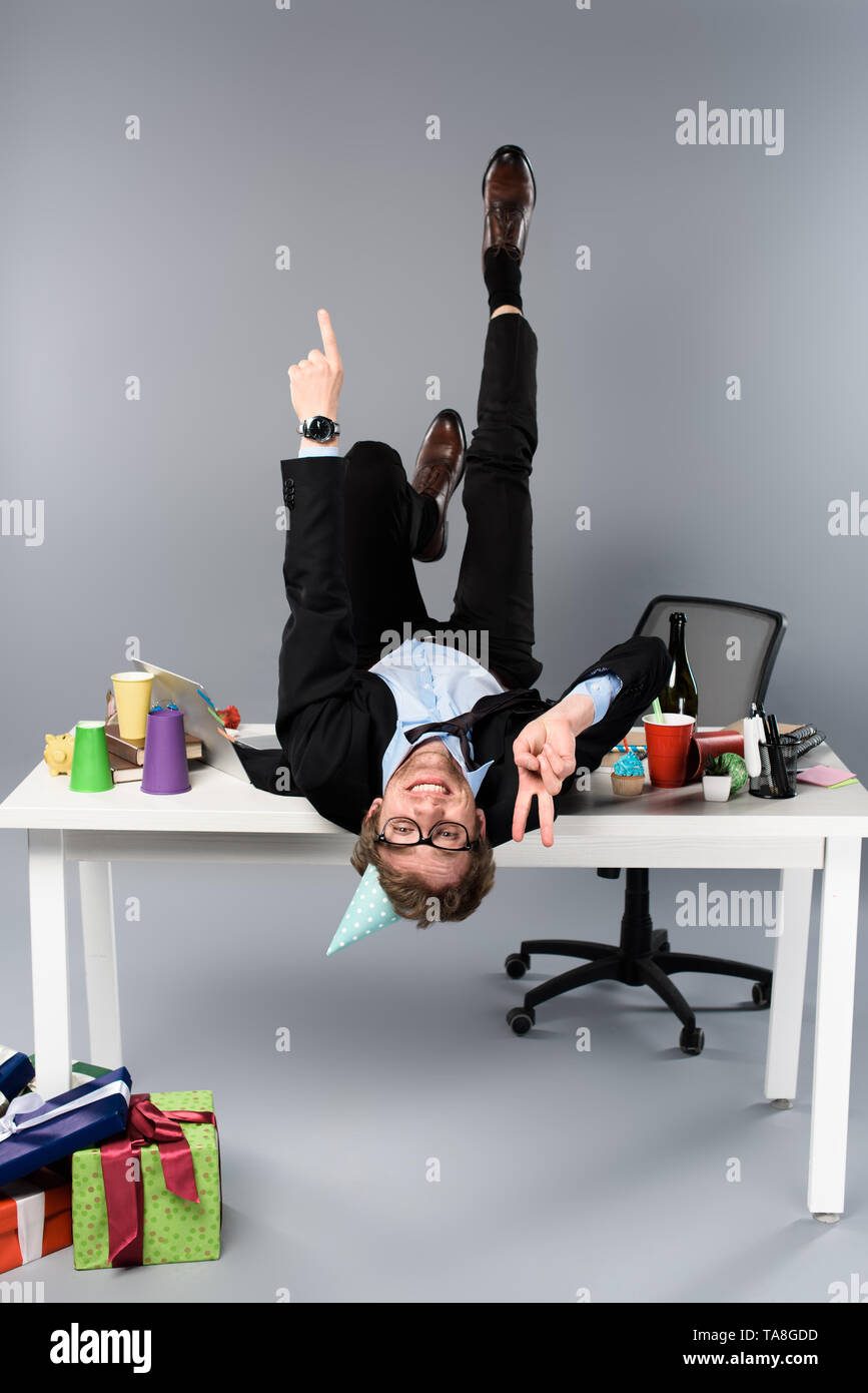 happy businessman in party cap lying on table at messy workplace and showing peace sign - Stock Image