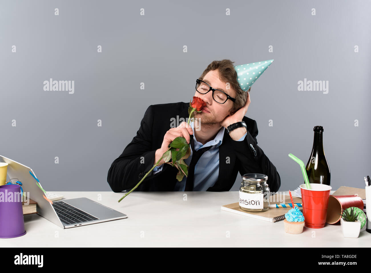 drunk businessman in birthday cap smelling rose at workplace - Stock Image