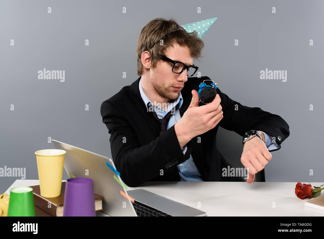 drunk businessman in party cap holding alarm clock and looking at watch isolated on grey - Stock Image