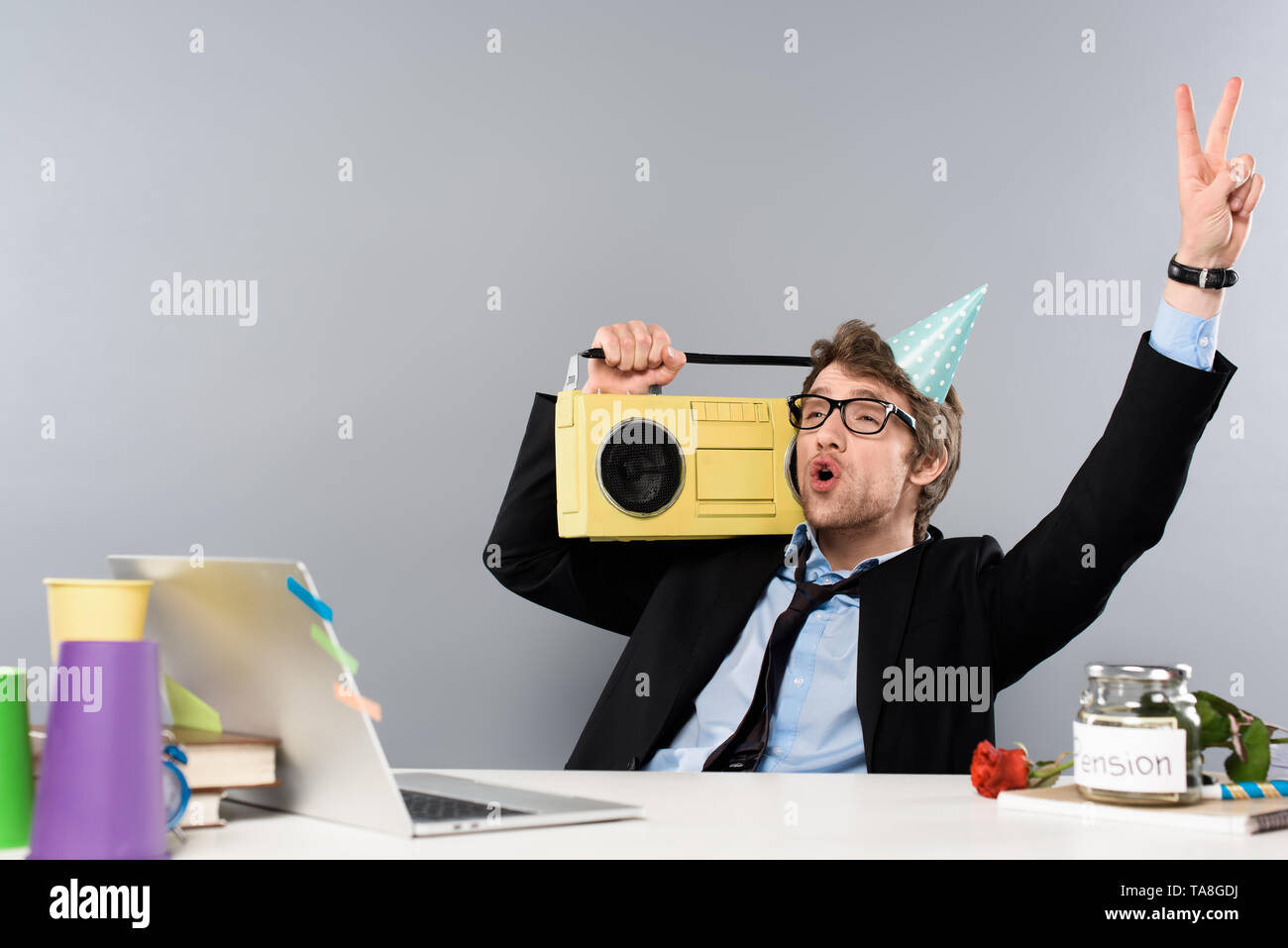 excited drunk businessman sitting at workplace in party cap with vintage tape recorder on grey background - Stock Image