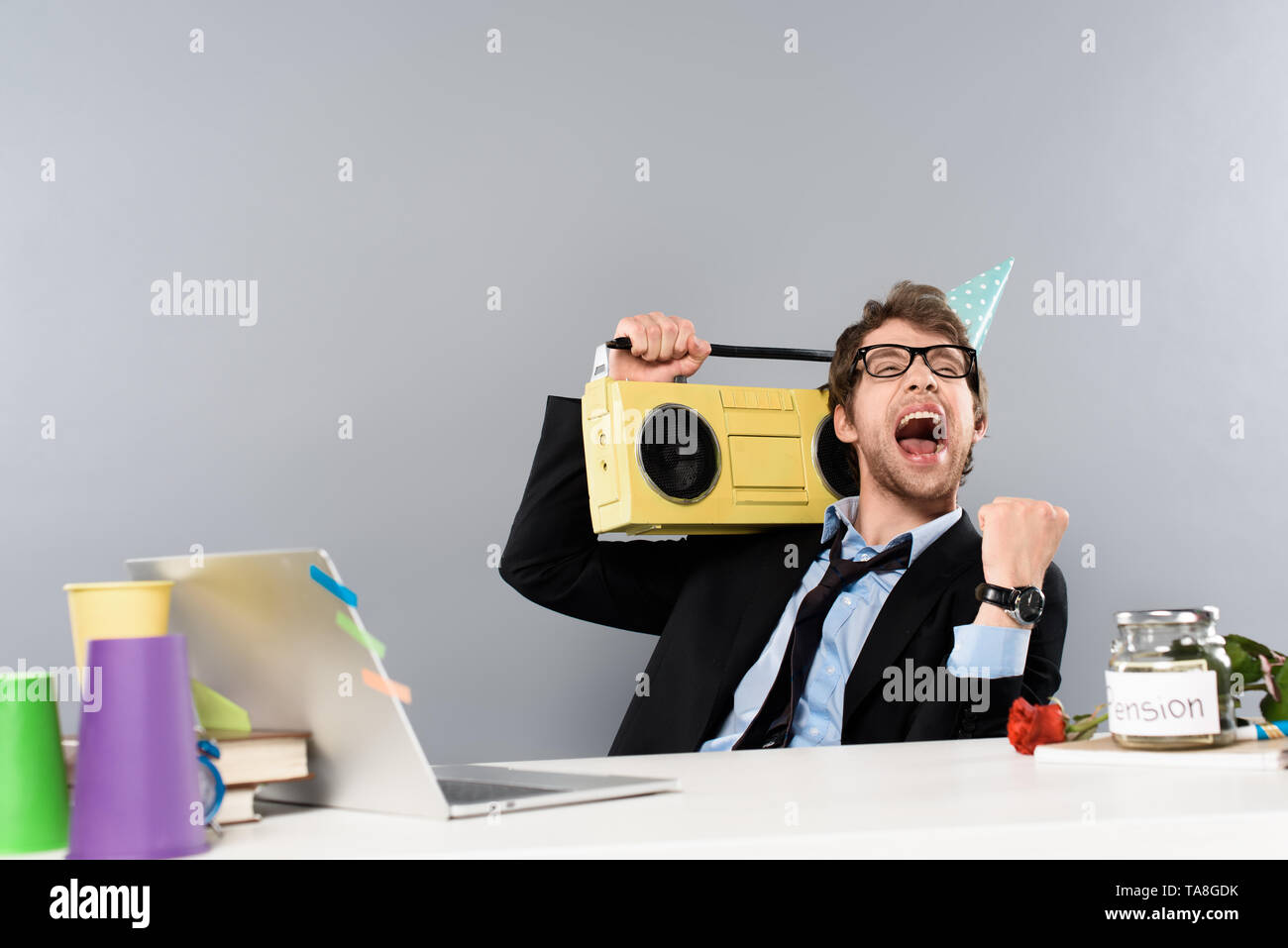happy businessman sitting at workplace in party cap with vintage tape recorder and rejoicing on grey background - Stock Image