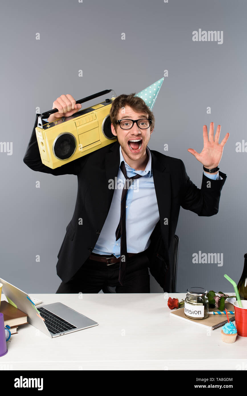 happy businessman at workplace in party cap with vintage tape recorder on grey background - Stock Image