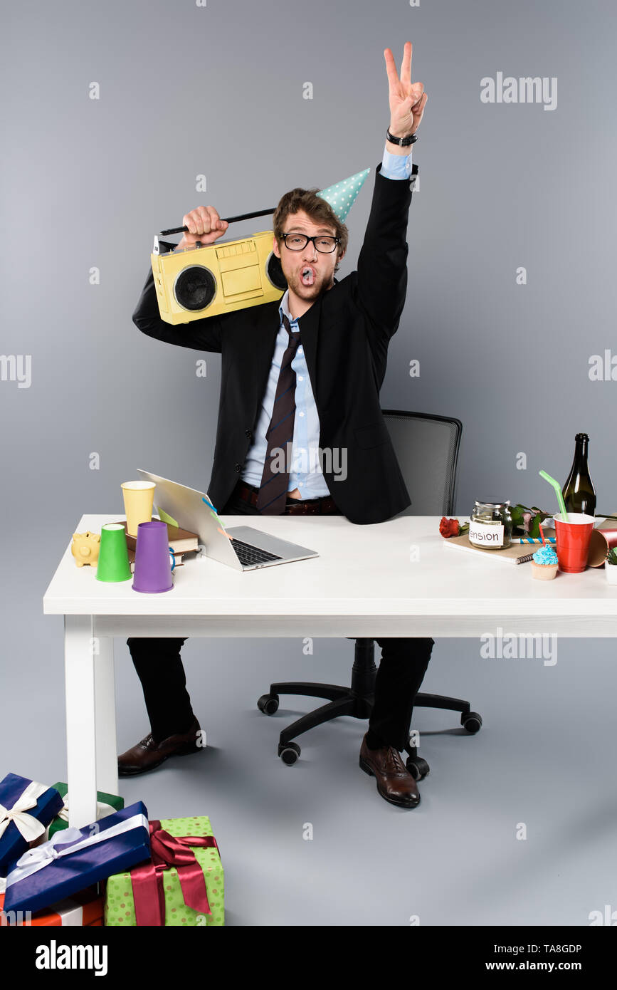 drunk businessman sitting at workplace in party cap with vintage tape recorder on grey background - Stock Image