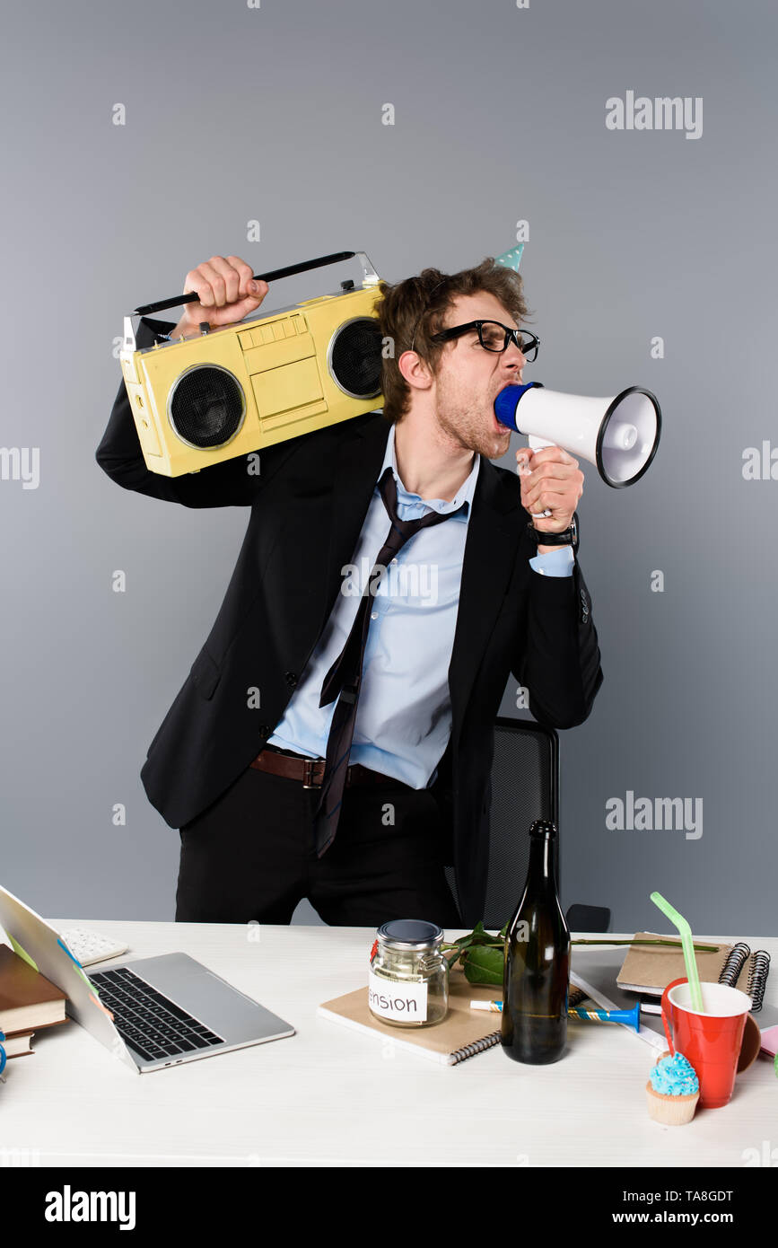 angry businessman at workplace in party cap holding vintage tape recorder and screaming in megaphone on grey background - Stock Image