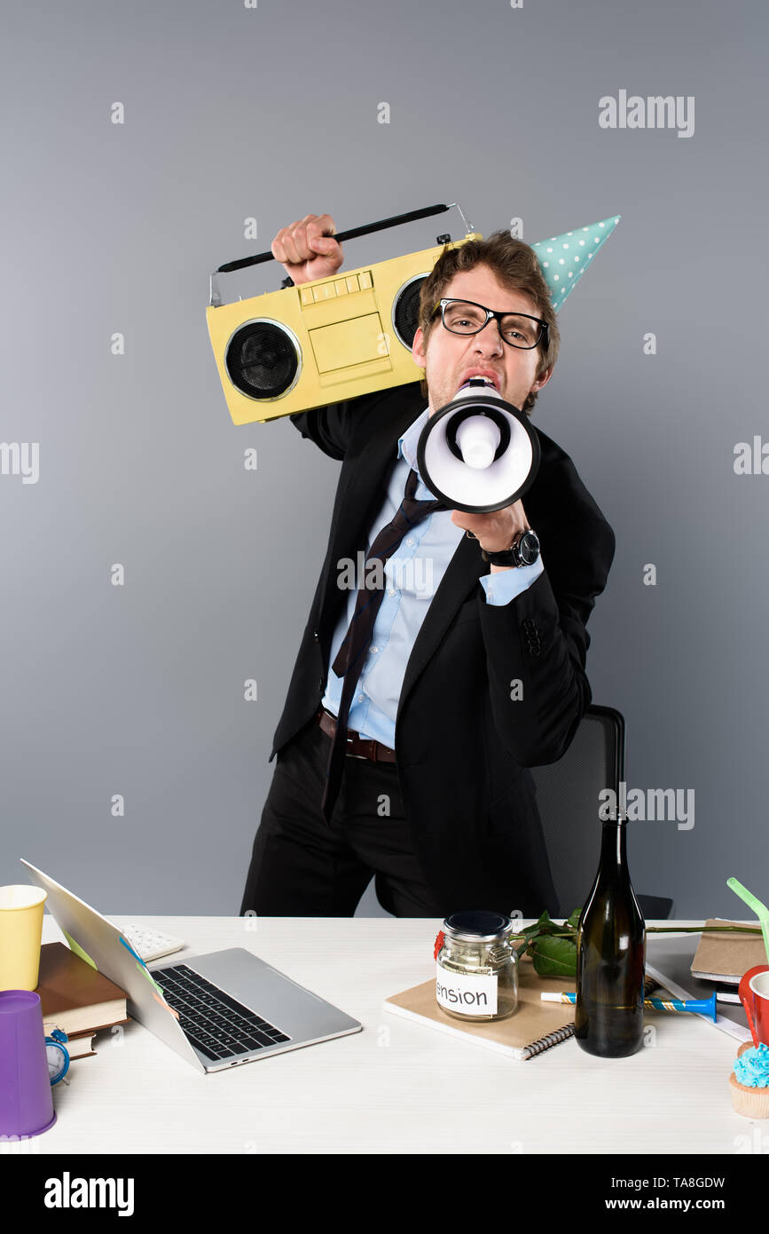 drunk businessman at workplace in party cap with vintage tape recorder screaming in megaphone on grey background - Stock Image