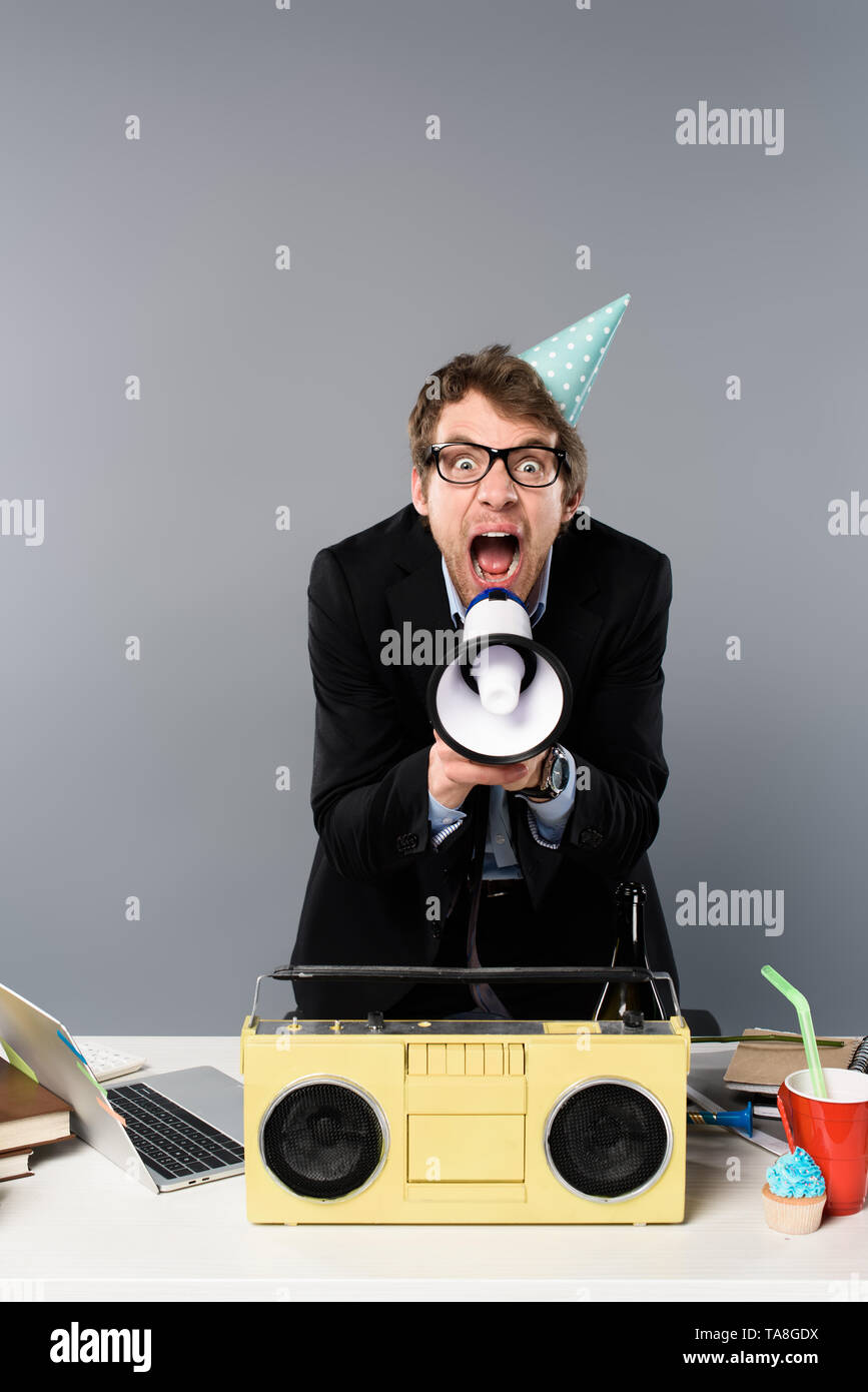 angry businessman at workplace in party cap near vintage tape recorder screaming in megaphone on grey background - Stock Image