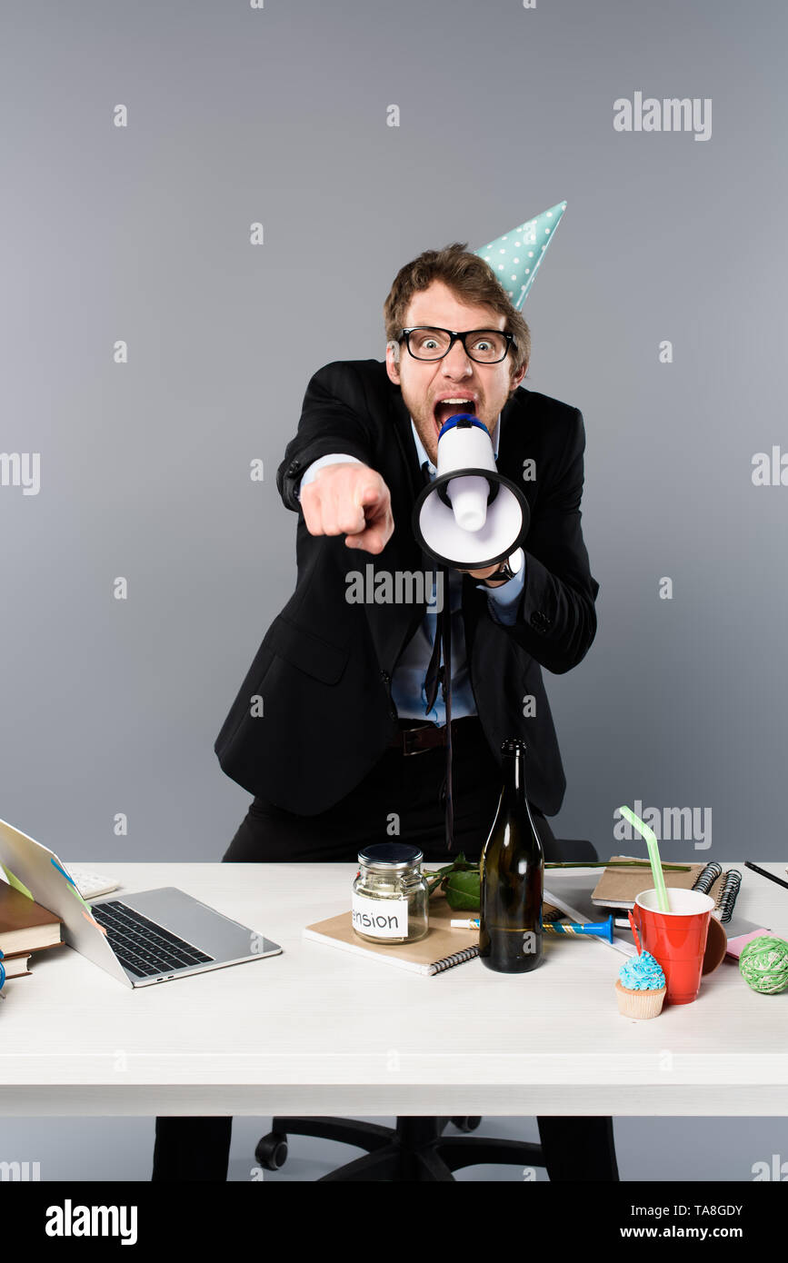 angry businessman in party cap screaming in megaphone and pointing with finger at camera on grey background - Stock Image