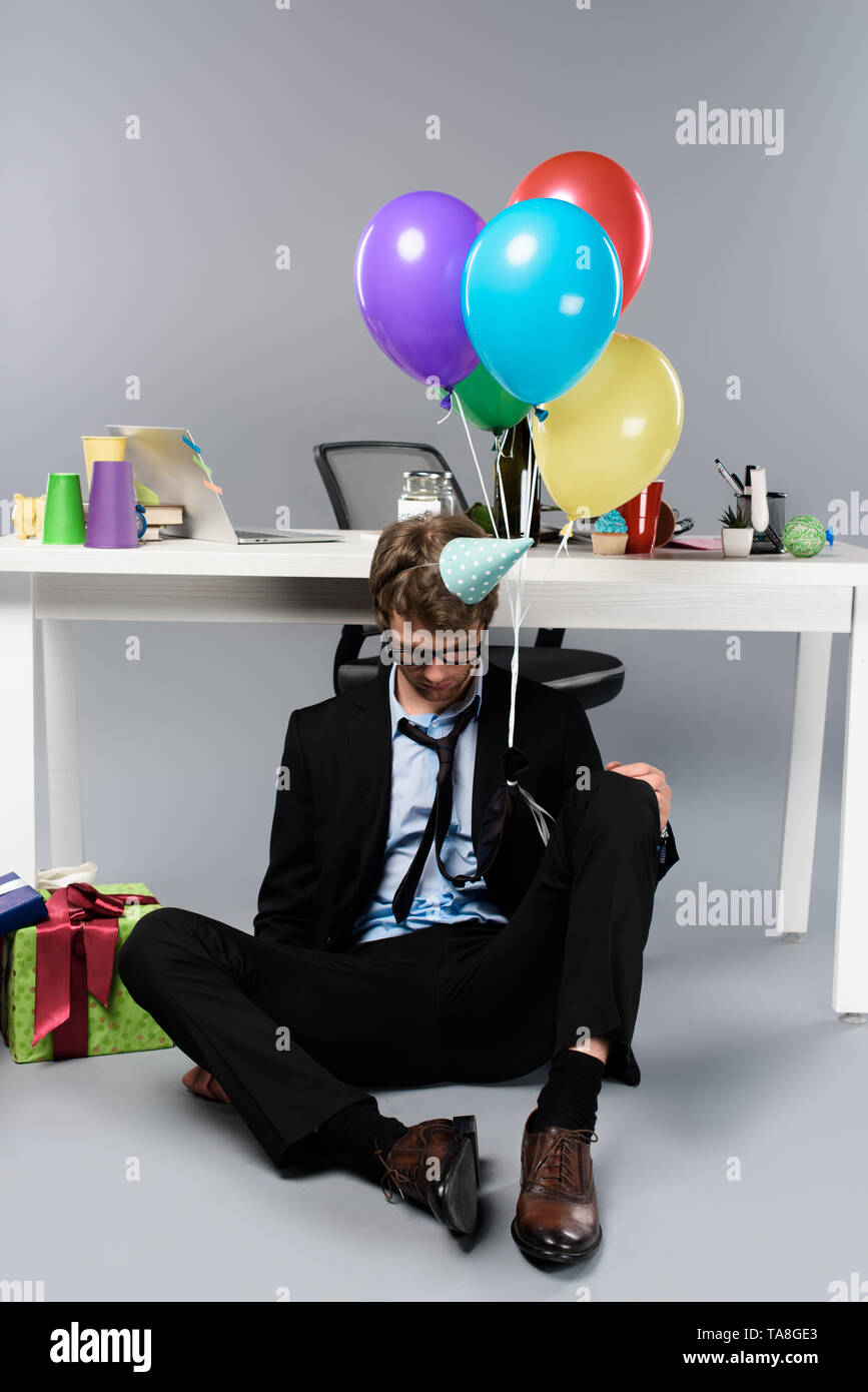 drunk businessman in party cap sleeping at messy festive decorated workplace - Stock Image