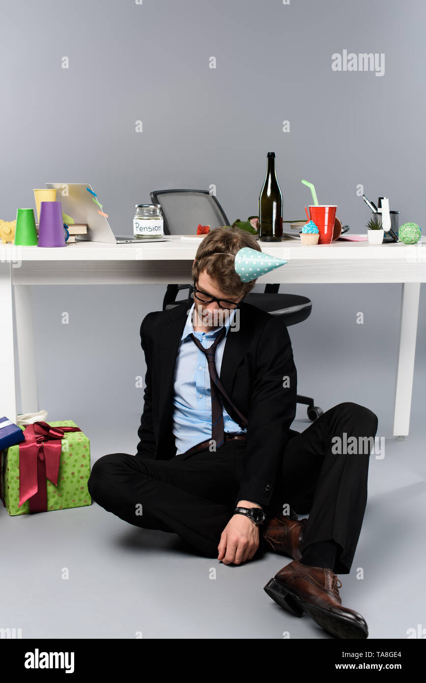 drunk businessman in party cap sleeping at messy workplace near presents - Stock Image